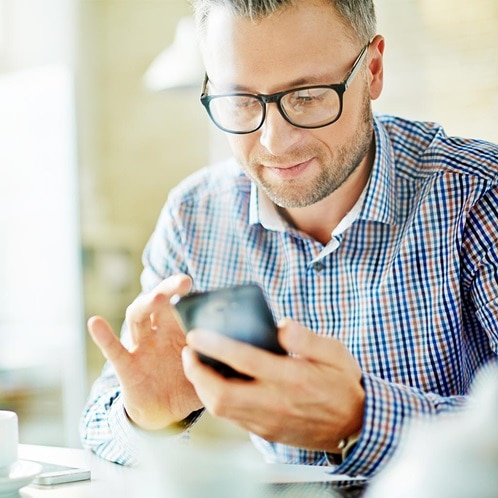 Ein Mann, der mit dem Handy seine Energiedaten über das Energiemanagementsystem flow abruft.