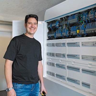 Lächelnde Person steht in einem Raum vor einem eingebautem Verteilerschrank von Hager.