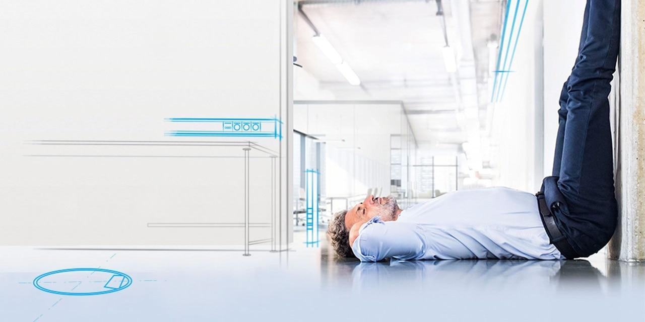 Mann liegt auf dem Boden und streckt die Beine hoch an der Wand