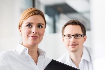Person nutzt myHager mit Tablet in der Hand, Mann im Hintergrund im Büro.