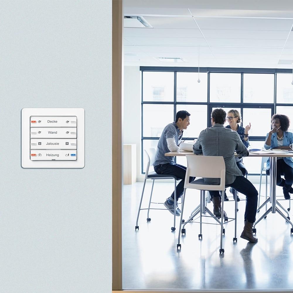 Gruppe von Mitarbeitern in einem Meeting-Raum. Im Vordergrund ein Berker Tastsensor 4fach Komfort, Q.1 polarweiß, mit individuell lackierten Schriftfeldern und gelaserter Beschriftung.