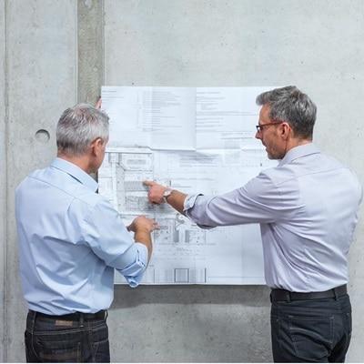 Zwei Personen schauen in einem Rohbau auf einen Bauplan.