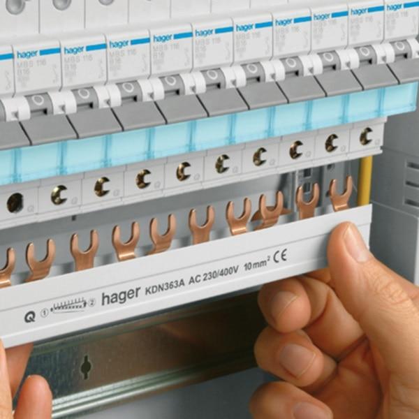 Die Hand eines Elektrohandwerkers montiert eine horizontale Phasenschiene an Reiheneinbaugeräte mit quickconnect