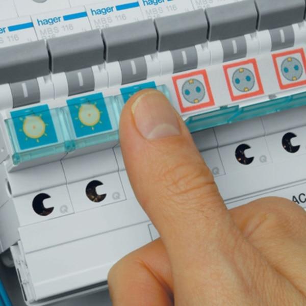 Eine Hand schließt die Schutzkappe über den Beschriftungsstreifen einer Reihe mit Leistungsschutzschaltern