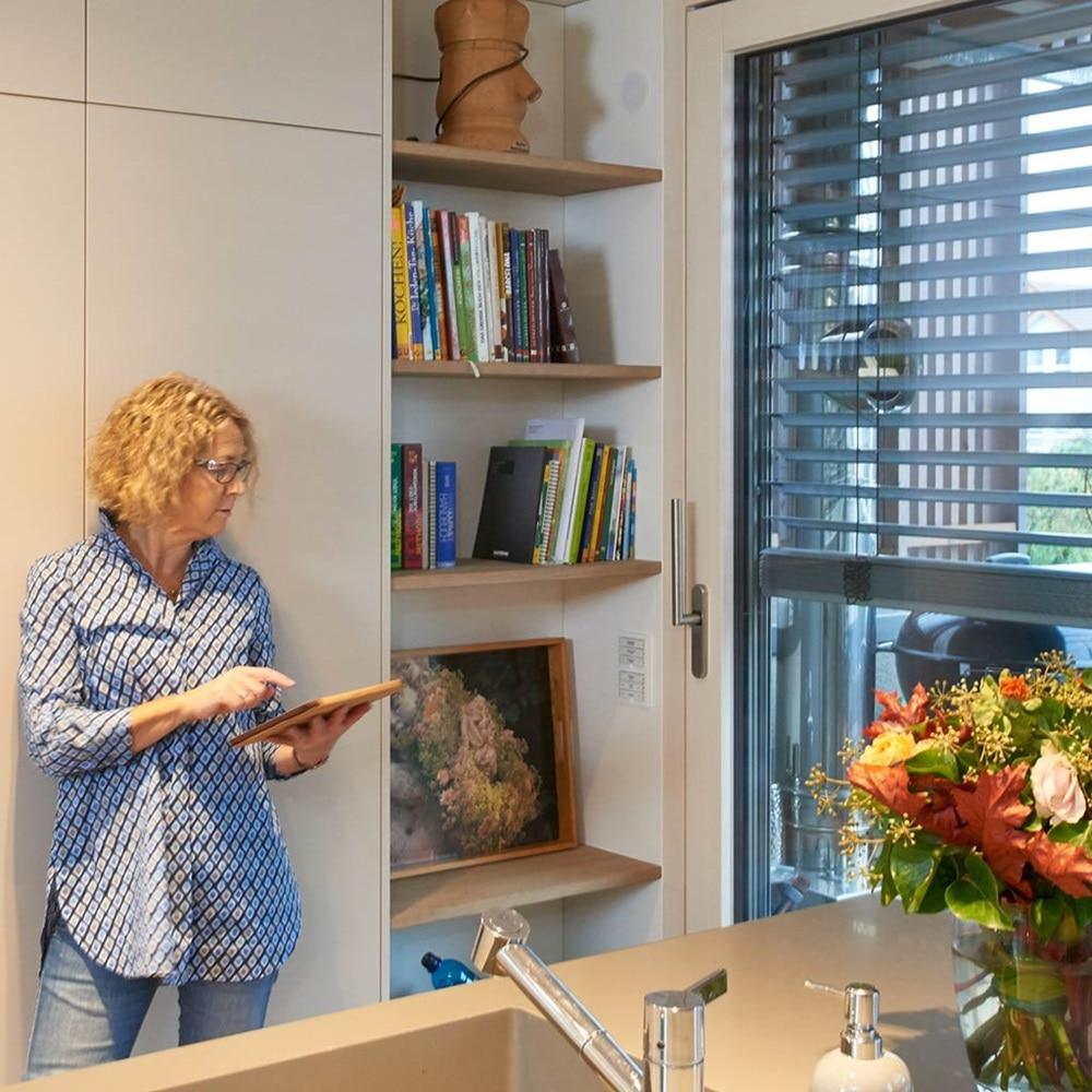 Frau bedient Smart Home mit Tablet, neben Berker Schalter.