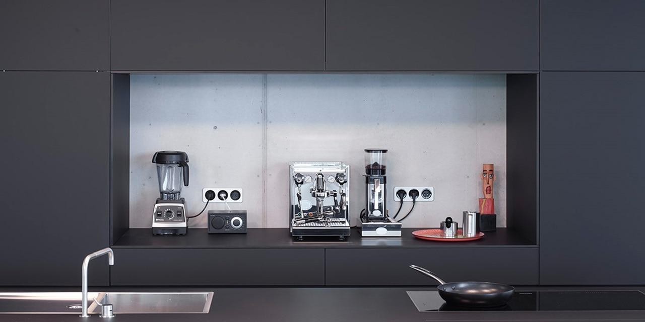 Küchenzeile mit Kaffeemaschine, -mühle und Mixer, angeschlossen an Steckdosen im Design der Serie Berker R.1