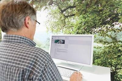 Bild eines Mannes, der vor einem PC sitzt.