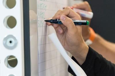 Bild einer Person, die an ein Whiteboard schreibt.