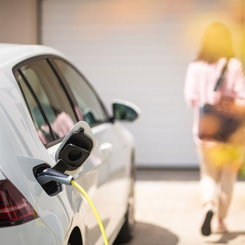 Ein Elektroauto hängt an einem Ladegerät, während es in einer Hauseinfahrt parkt