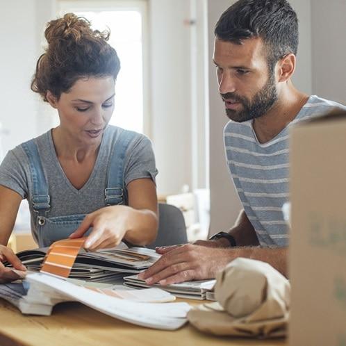 Eine Frau und ein Mann planen ihr Eigenheim gemeinsam an einem Tisch.