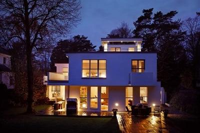 Ein beleuchtetes Einfamilienhaus im Dunklen